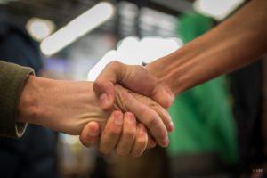 Image d'une poignée de main symbolisant l'échange entre riverains et réfugiés.